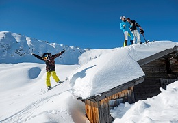 Kitzbueheler-Alpen_Skiers_Family on roof of hut_Child jumpning with snowboard_@StefanEisend